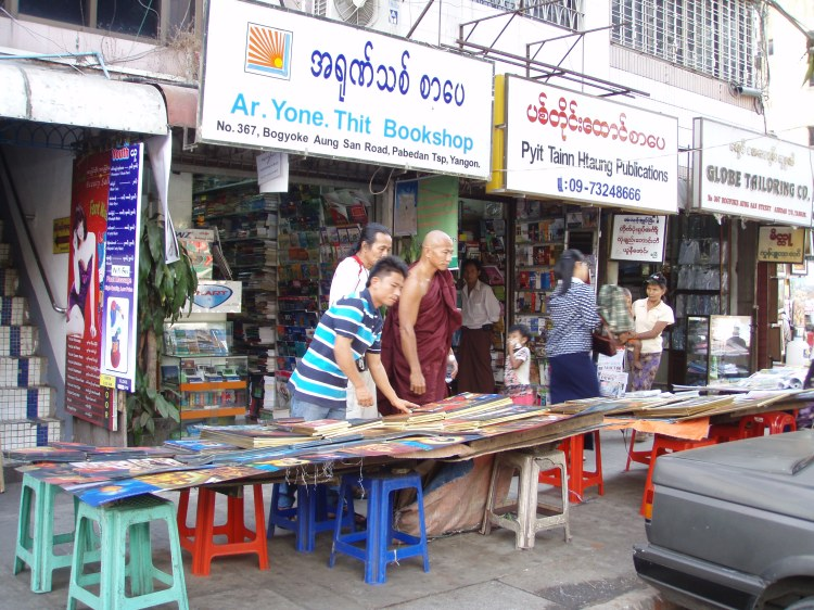 A sinewy monk in saffron leans over a table with booksellers at Yangon's bustling Bogyoke market.