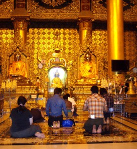 Buddhist visitors take a moment for contemplation before Buddha images at the Shwedagon