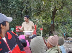 An itinerant Buddhist preacher solicits alms in our truck on route to Golden Rock pagoda.